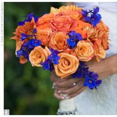 Orange and Blue Wedding Bouquet  Blue delphiniums popped against three types of orange roses. For extra glamour, the stems were wrapped in satin adorned with rhinestones