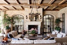 Outdoor loggia with chandelier and sconces, reclaimed-oak ceiling beams and antique limestone mantel.