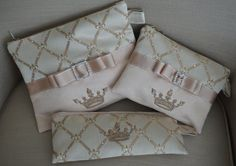 """NEW Crown Cosmetic Cases coordinate with our Crown Totes. Gorgeous faux suede and damask fabric. Small size is solid brocade fabric with embroidered crown and Swarovski crystal accents. Small is oblong and perfect for your makeup brushes, combs and longer makeup tools. Medium and Large are split fabric design and are accented with Swarovski crystals, embroidered crown, ribbon trim and bow with rhinestone buckle. This crown pouch is available in 3 Sizes: Small (10"""" x 5""""), Medium (8"""" x 6.5"""")…"""