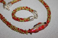 Handmade Glass Fish make a perfect focal bead for a kumihimo necklace. Silver endcaps finish off this great look!