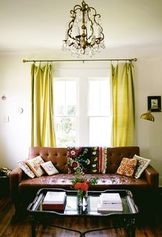 I'm attracted to the eclectic combination of textiles in this space. Also, the shape and texture afforded by the leather coffee table are just lovely.