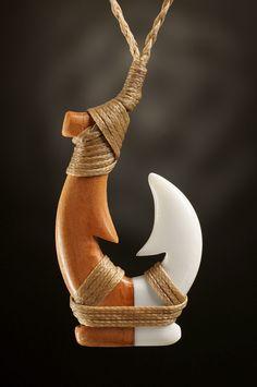 Schmuckanhänger Hei Matau aus Rinderknochen und neuseeländischem Holz.  Ein beeindruckender Matau in der Kombination aus Knochen und Holz sowie mit einer traditionellen Bindung.  Wird nur in limitierter Stückzahl angefertigt.  Die symbolische  Bedeutung des Hei Matau (Angelhaken) steht für Stärke, Willenskraft, Wohlstand, Frieden wie auch für eine sichere Reise über das Wasser.
