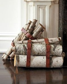 love the idea of simple leather strap around logs to keep them neat indoors