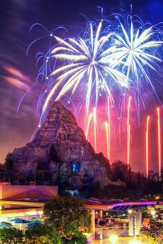 The color from the fireworks is reflected on the rock structure. There is also colored light radiating from the neon lights below.
