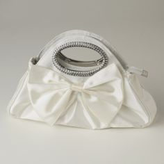"""This stunning bow tie evening bag is beautiful and fun! Rhinestone accented silver handles truly make this a one of a kind accessory. Zipper closure and inside side pocket with chain included that can be worn with or without.  Size: 12"""" (Length) 8"""" (Height) 2"""" (Width)"""
