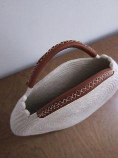 Sacchetto bianco rotondo fatto di corda di cotone e pelle marrone riciclata. Questa borsa è durevole e abbastanza spaziosa per adattarsi a tutte le vostre necessità - misure circa 12 pollici e 2 pollici profondo, con circa 3 pollici maniglie. Trovare una borsa di basket in semplice