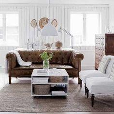 Przytulny pokój wypoczynkowy z sofą Chesterfield w roli głównej. Ciemnobrązowa komoda to antyk, który przyjechał z Chin, stolik z lat 70. jest pamiątką po mamie Heleny.