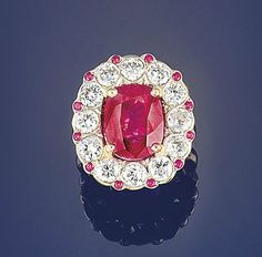 A ruby and diamond cluster ring   The oval cushion-cut ruby in claw mount to a collet-set brilliant-cut diamond surround with ruby points, pierced gallery and plain hoop