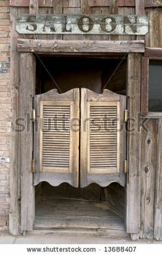 Old Western Swinging Saloon Doors with a Saloon Sign Above Doors - stock photo