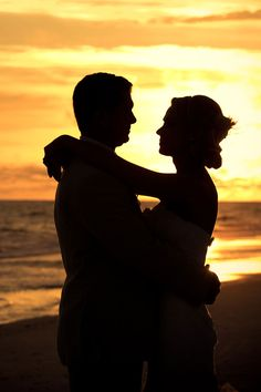 silhouettes against the sunset...must have photo for beach wedding