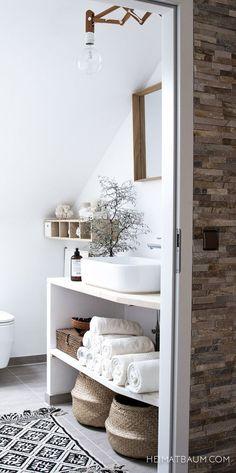 Et lækkert enkelt og naturligt badeværelse i varme farver i form af træ, grå og hvide farver.