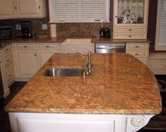 Kashmir gold granite kitchen countertop with white cabinets.