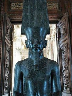 Amun statue with the features of his 'living image, or TutankhAmun, with the deity's characteristic feathers and goatee postiche beard. 18th dynasty.