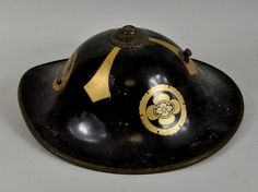 "Japanese lacquer Jingasa parade helmet with Mon decoration, 19th century. 6 1/2"" high, 14"" long."