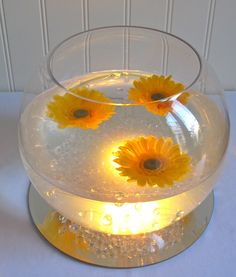 Goldfish Bowl with coloured led light, acrylic stones and beads, floating gerberas and a mirrored base.