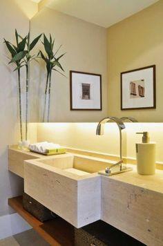 O mármore travertino foi utilizado para fazer a bancada e esculpir a cuba deste lavabo de autoria de Débora Aguiar. Sob ele, uma prateleira de madeira armazena cestos de fibras naturais para armazenar objetos