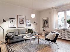 salon scandinave aménagé avec un canapé gris, deux tables basses rondes et un tapis scandinave à motifs géométriques gris
