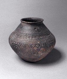 Pottery urn of brown ware, biconical; triple-groove chevrons round girth, spaces filled with stamped circles, wheels & triangles; row of cross-in-circles & grooves above shoulder; hole in base.