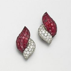 PAIR OF INVISIBLY-SET RUBY AND DIAMOND EARCLIPS, FRENCH, CIRCA 1950. The stylized paired foliate motifs invisibly-set with numerous calibré-cut rubies and 60 round pavé-set diamonds weighing approximately 4.00 carats, mounted in platinum, signed France, French assay marks.