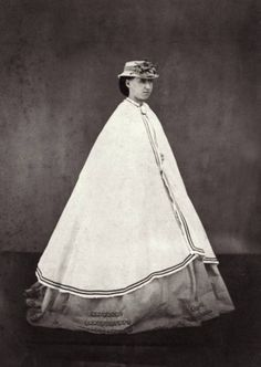 circa 1865: A woman wearing a long cloak over her dress