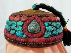 Unusual Antique Tibetan Pilgrims Cap lavishly encrusted with natural Turquoise nuggets, agate, and horn beads was handcrafted approximately 100 years ago in the Tibetan Autonomous Region (Xizang). The crown on this unique cap is made of old embroidered textile, with a swinging top-knot that is embellished with natural Turquoise and cowrie shells. When not being worn, these caps were carried by their top-knots, which often had to be replaced when they broke or wore through.
