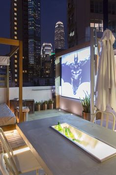 Rooftop area, evening view. Operable projector & projector screen that be hidden away into a wooden frame that is controlled by a Crestron home automation system. Concrete dining table with built in ice bucket & drainage system.