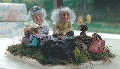 A elderly fairy couple viewing a movie while enjoying popcorn & soda.  Sculpted by Susan Nordella