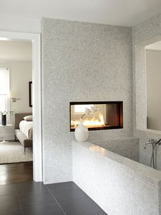 We love the sleek and modern tile in this space! More tile fireplace design ideas: http://www.bhg.com/decorating/fireplace/styles/tile-fireplace-design-ideas/?socsrc=bhgpin082013bathtub=17