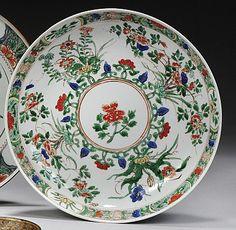 CHINE Époque KANGXI (1662-1722) Coupe en porcelaine décorée en émaux polychromes de la famille verte de bouquets fleuris autour d'un médaillon de pivoine, l'aile décorée de quatre réserves de fleurs sur fond de sapèques et fleurs. Diamètre : 22 cm