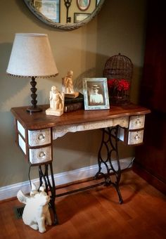 Antique seeing machine used as a side table. I painted the drawers and front with General Finishes Antique White and sealed with their high performance top coat in flat. I also distressed it a bit to show off the beautiful details.
