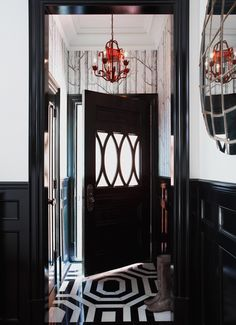 """I Love the feel of this entry. The first element that captured my love is the custom black and white octagon floor.... it is stunning! Lovely element number two is the complimentary """"woods"""" wallpaper... ahh just perfect; and to top it off a pop of color in the red chandelier."""