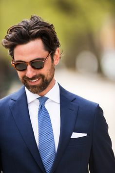 Classic combination of navy single-breasted suit, blue textured tie, and white cotton pocket square