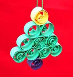 Strips of construction paper, a piece of yarn and some glue turn into this fun little quilled paper Christmas tree ornament.