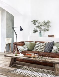 White walls, brown leather sofa, aged wood bench/coffee table, black floor lamp, natural carpet.