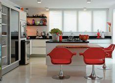 Cozinha branca e preta + piso claro + bancada de madeira + cadeiras vermelhas. Via Casa Cláudia Premium.