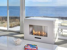 This minimal, white fireplace adds a cozy touch to the oceanfront serenity.