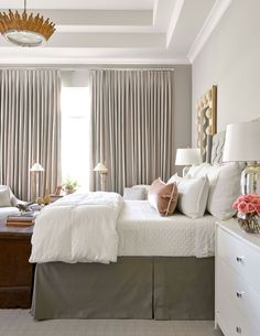 The subdued tones from the rest of the house carry into this space, where white bedding from Pom Pom at Home dresses a bed upholstered in gray linen. - Photo: Nathan Schroder / Design: Julie Dodson