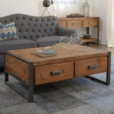This roughly finished wood coffee table sits on a durable black metal frame. Two drawers on each side open for hidden storage and open with black metal pulls. This rustic coffee table is a warm accent