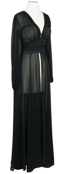The sheer black 1940's Long Robe is a stunning, ankle-length gown that combines the bodice of our 1940s Button Blouse with the long, billowing sleeves of the Bianca Dress. This vintage-inspired robe is the perfect fusion of elegance and sophistication. With a three-panel structured waist for a flattering vintage silhouette and a deep v-neck to accentuate your décolletage, the gown opens at the front with petite covered buttons. The long length skirt splits from the waist, making this design…