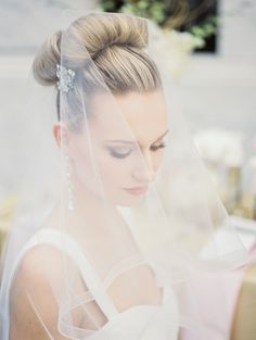 Soft tulle veil over a top knot bun.   Photography: Studio Elle Photography - studioellephotos.com  Read More: http://www.stylemepretty.com/2014/06/26/gold-and-blush-wedding-inspiration-at-the-cleveland-museum-of-art/