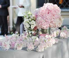 A towering centerpiece of roses, grapes and tall candles tops a luxe purple table.