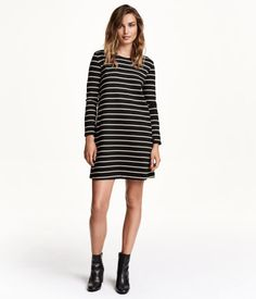Long-sleeved, A-line dress in thick jersey with side pockets, concealed zip at back, and slits at cuffs.