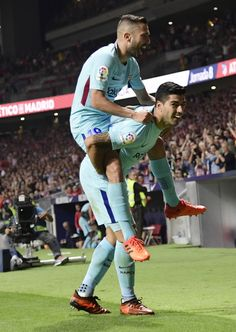 Barcelona's Uruguayan forward Luis Suarez (bottom) celebrates a goal with Barcelona's Spanish defender Jordi Alba during the Spanish league football match Club Atletico de Madrid vs FC Barcelona at the Wanda Metropolitano stadium in Madrid on October 14, 2017. / AFP PHOTO / JAVIER SORIANO