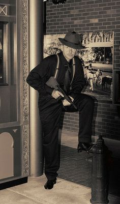 """This is a picture of a gangster from the 1920's. They used Thompson sub-machine guns aka the """"Tommy Gun"""" which is the gun in his hands."""