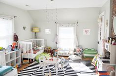 Bright and cheery shared nursery - we love that play is at the center of this room!