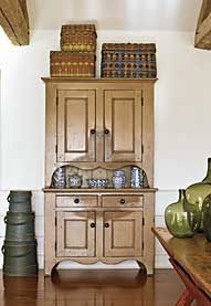 """The New Jersey step-back cupboard with dramatic scalloping retains its original tan paint. """"I think the wear pattern is as interesting as the paint,"""" says Patrick Bell. """"It becomes a design element."""" Woodlands baskets provide color on top of the cupboard, as does the graduated stack of firkins with original blue paint. Displayed on the cupboard is a portion of the wife's extensive collection of blue-decorated spongeware. The nineteenth-century New England sawbuck table retains its original…"""