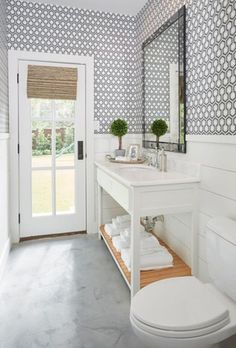 Clean, white shiplap walls and ornate hexagonal wallpaper make a perfect pair in this powder room.