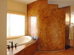 Latin colors and handcrafted elegance accentuate this bold master bathroom. The concrete tub deck and large shower provide a continuous flow with a backdrop of city lights below.