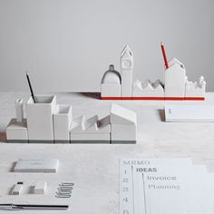 Deskstructure Desk Organizer: It Takes A Village. The Deskstructure desk organizer is comprised of building-shaped containers that line up to create the appearance of a warehouse or city skyline. The set contains both lidded and open containers perfect for clips, writing instruments, business cards and other supplies. Move the containers around to create your own custom skyline.