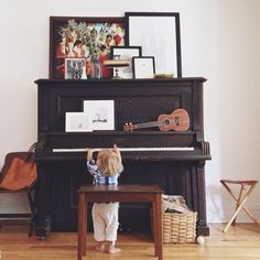 This reminds me of my house.  I always have my ukulele on my piano, and my piano light is gold too. :)
